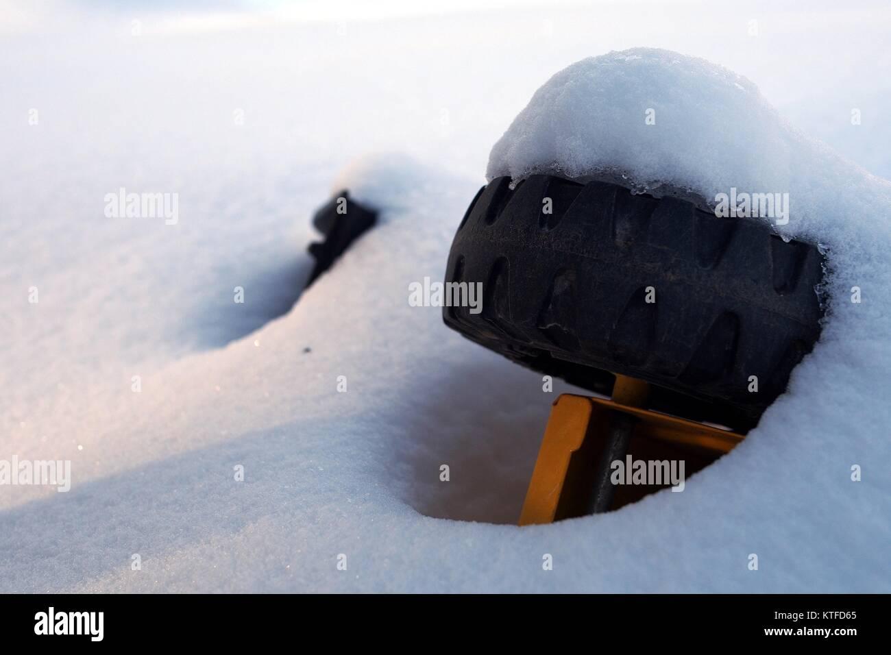 Metal toy truck wheel poking through the fresh snow in a Glebe park, Ottawa, Ontario, Canada. - Stock Image