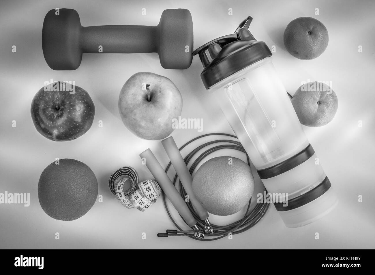 The concept of a healthy diet. Dumbbells, shaker, rope, bananas, oranges, roulette, oranges, red apple, green apple, - Stock Image