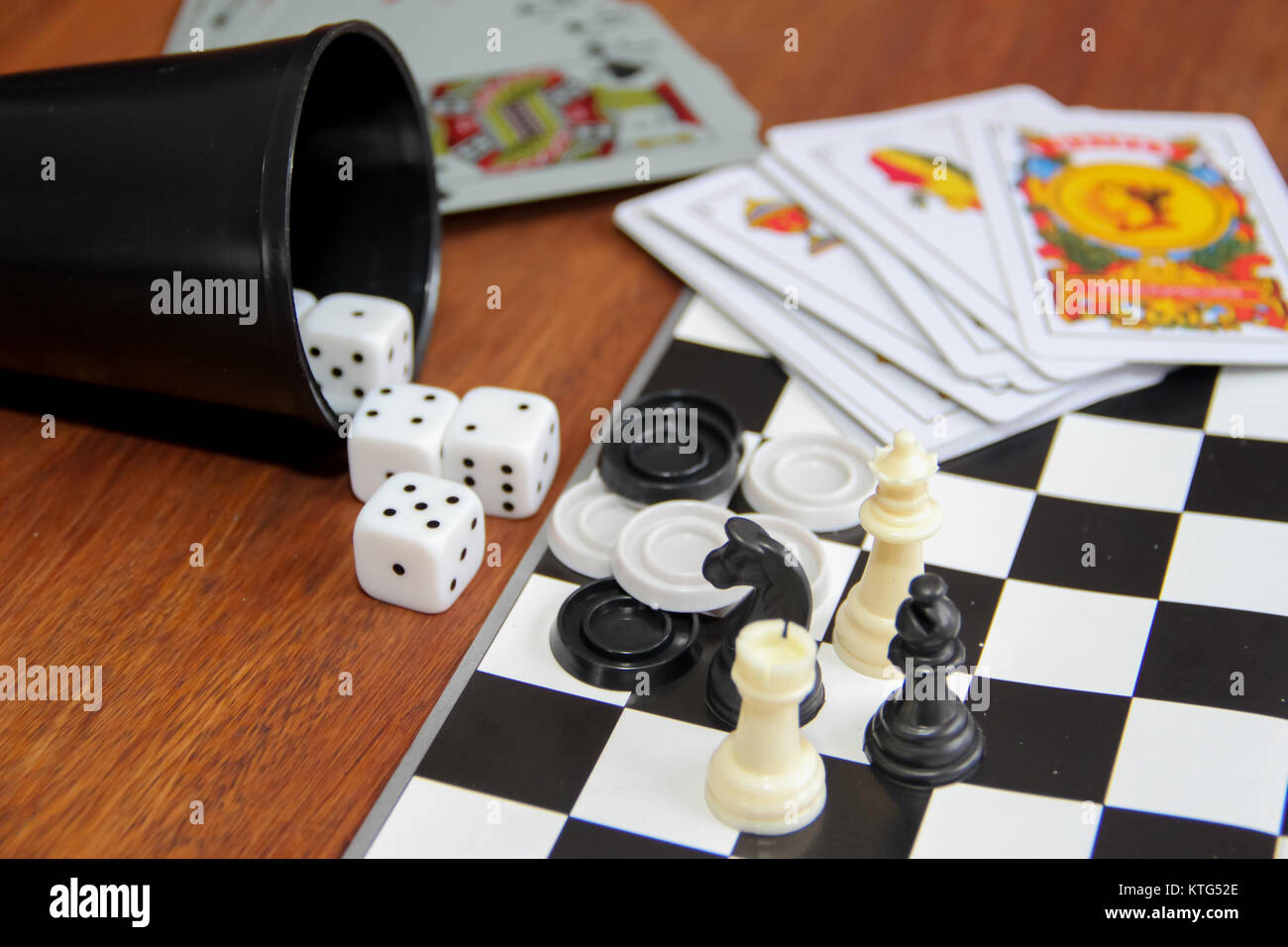 mix of goblet table games dice spanish poker cards chess and checkers Stock Photo