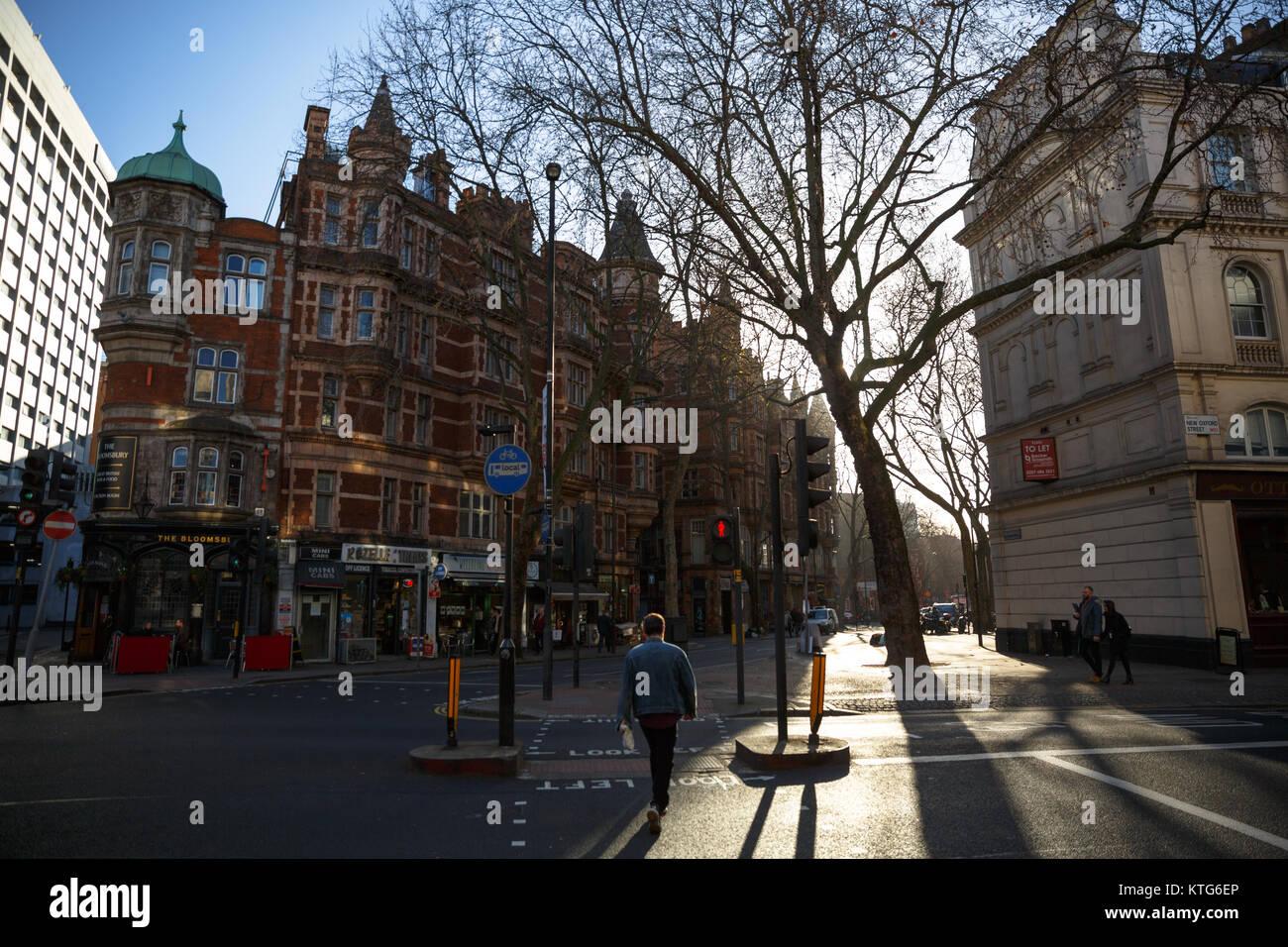 People walking outside on sidewalk during sunset in Bloomsbury - London, England, UK - Stock Image