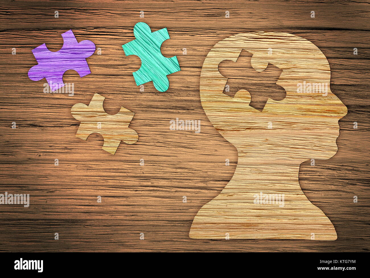 Puzzle head brain concept. Human head profile made from brown paper with a jigsaw piece cut out. - Stock Image