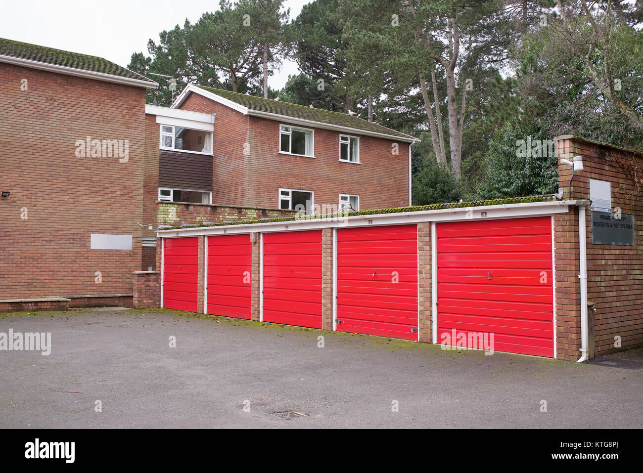 Garages with red doors and flats complex - Stock Image