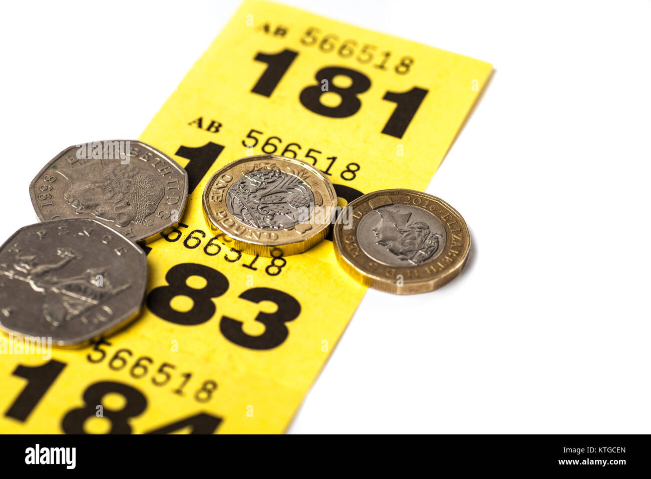 strip of yellow raffle tickets with uk coins stock image