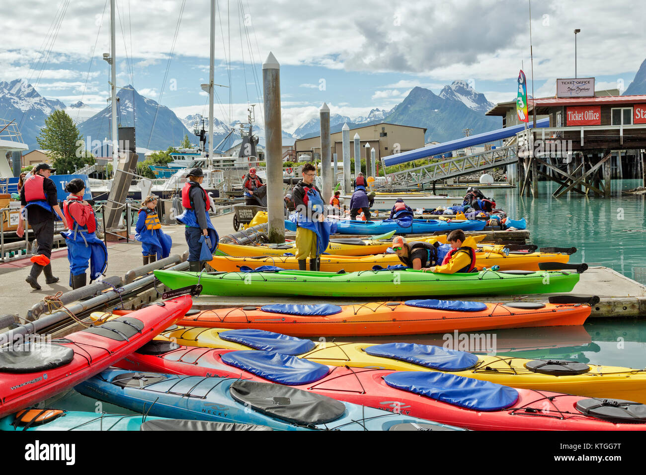 Kayakers wearing safety gear, receiving instructions prior to departing small boat harbor. - Stock Image