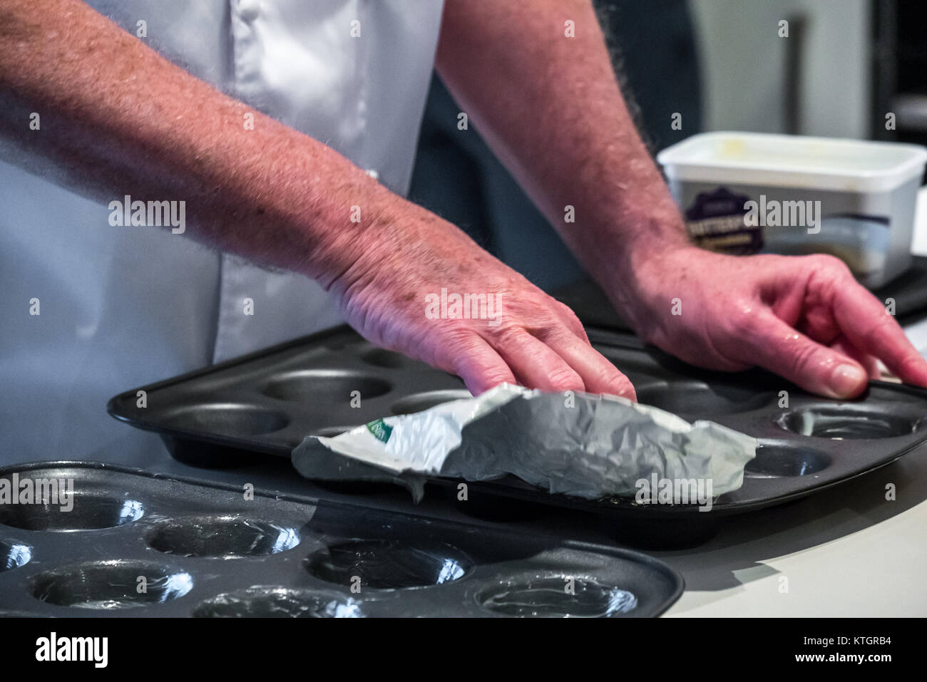 Close up of older man's hands greasing mince pie tins in a kitchen in preparation for making mince pies Stock Photo