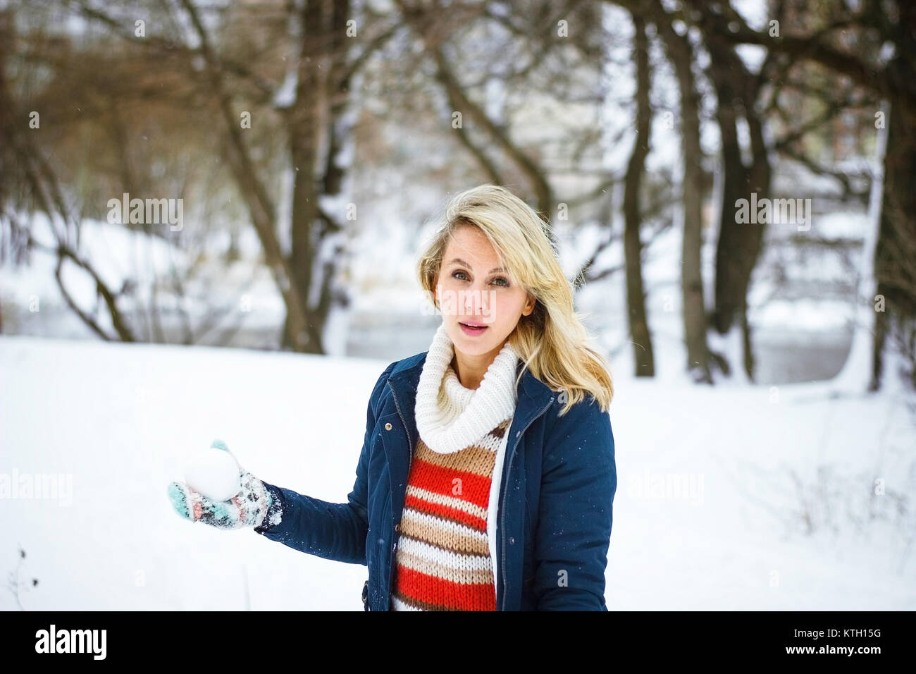 Winter girl play snowballs - Stock Image