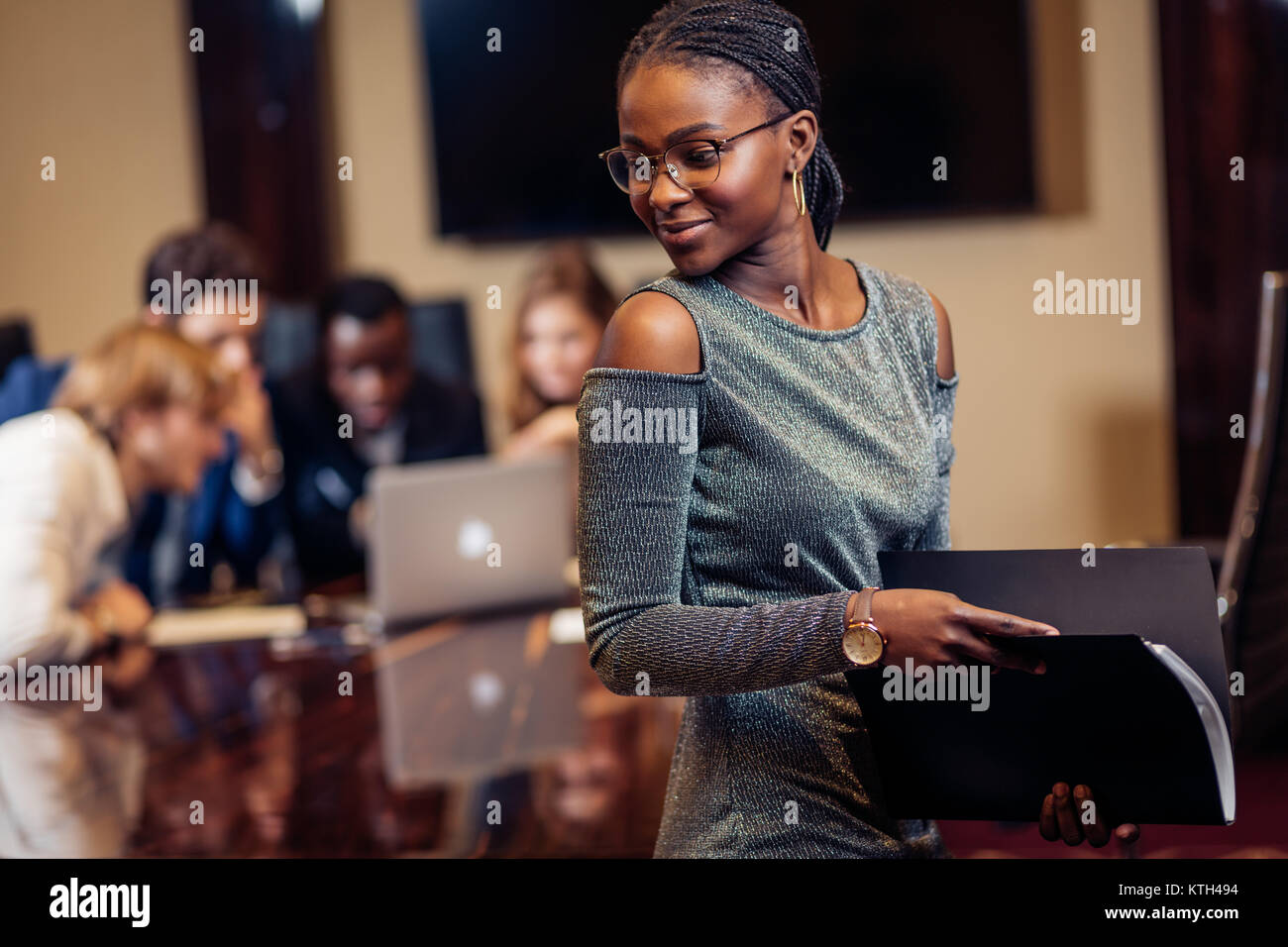 African businesswoman look at camera in boardroom with colleagues in background - Stock Image