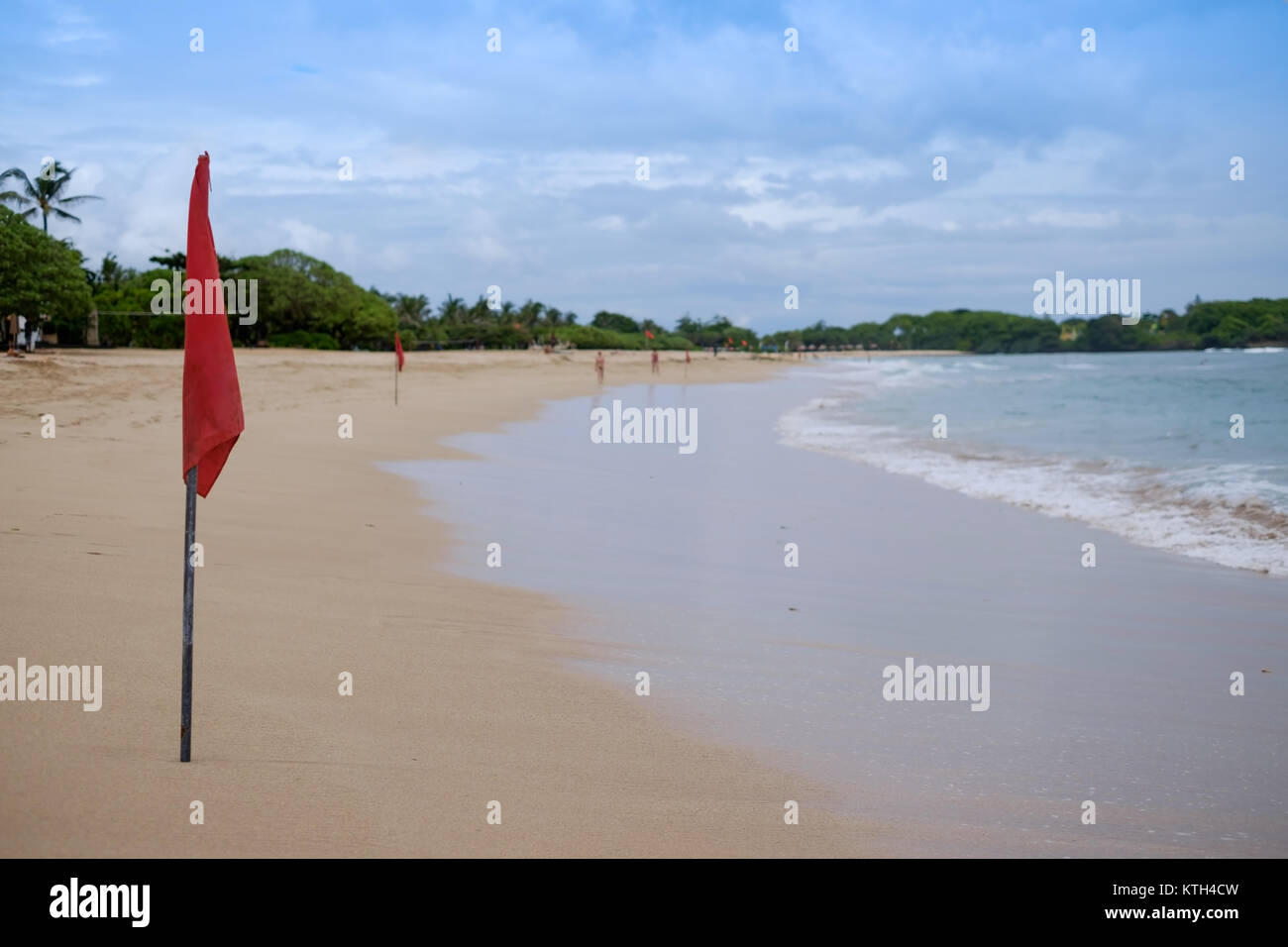 A red warning flag on the beach in the Nuca Dua Bali, Indonesia. Danger to swim in ocean - Stock Image