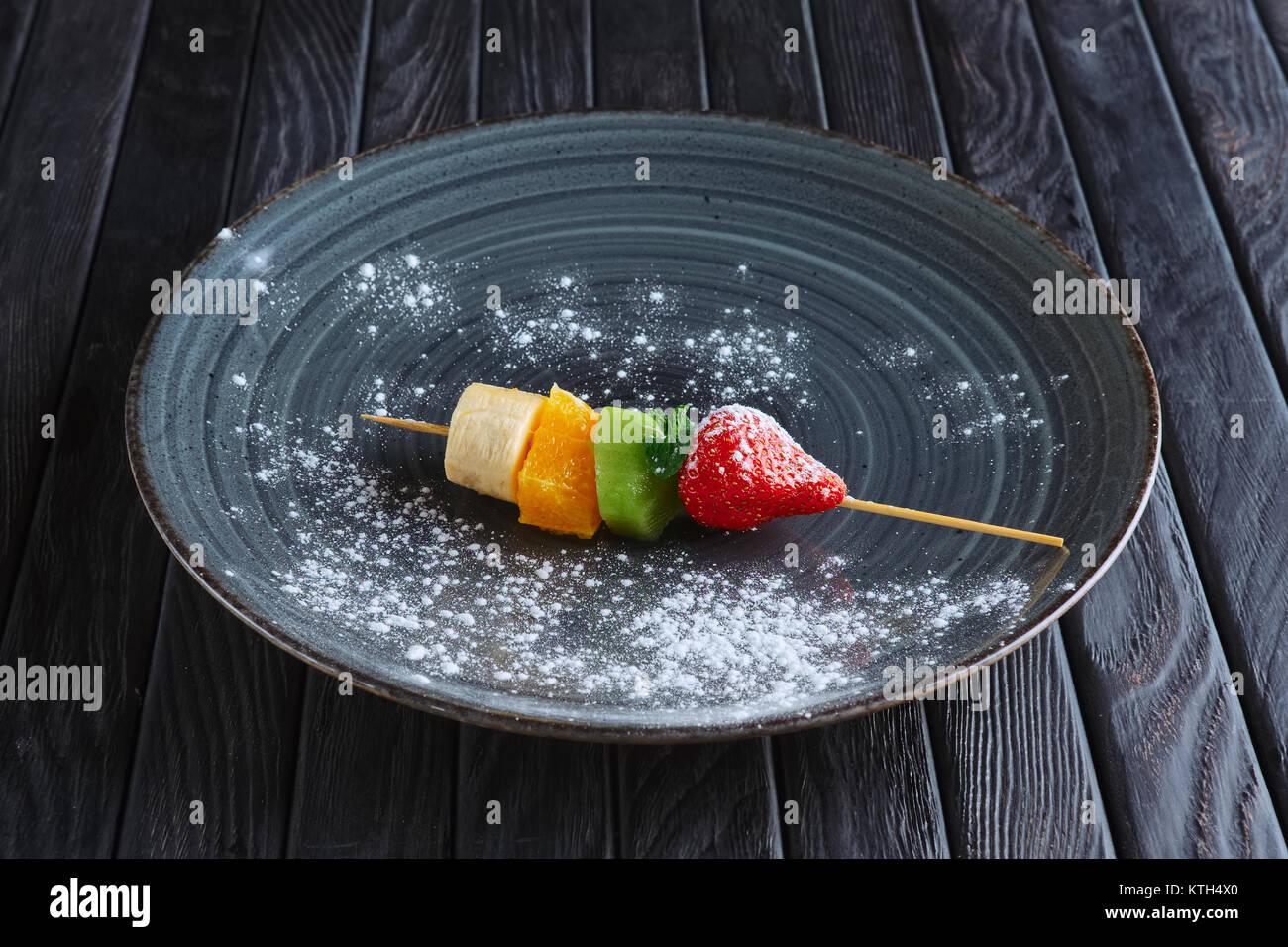 Appetizer for reception. Fresh banana, orange, kiwi, strawberry on skewer - Stock Image