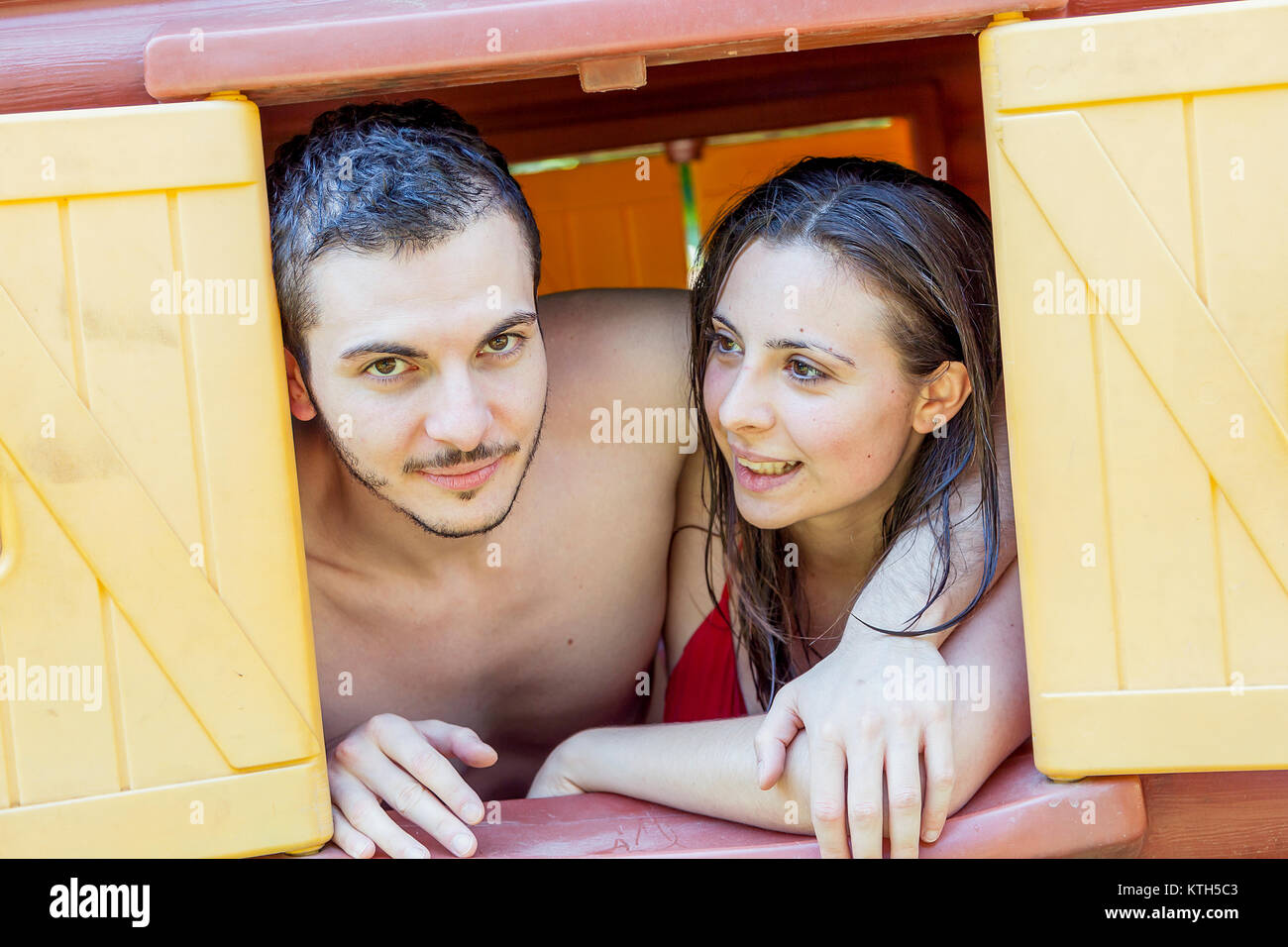 Couple portrait of lovers in swimwear looking out to window of a toy house - Stock Image