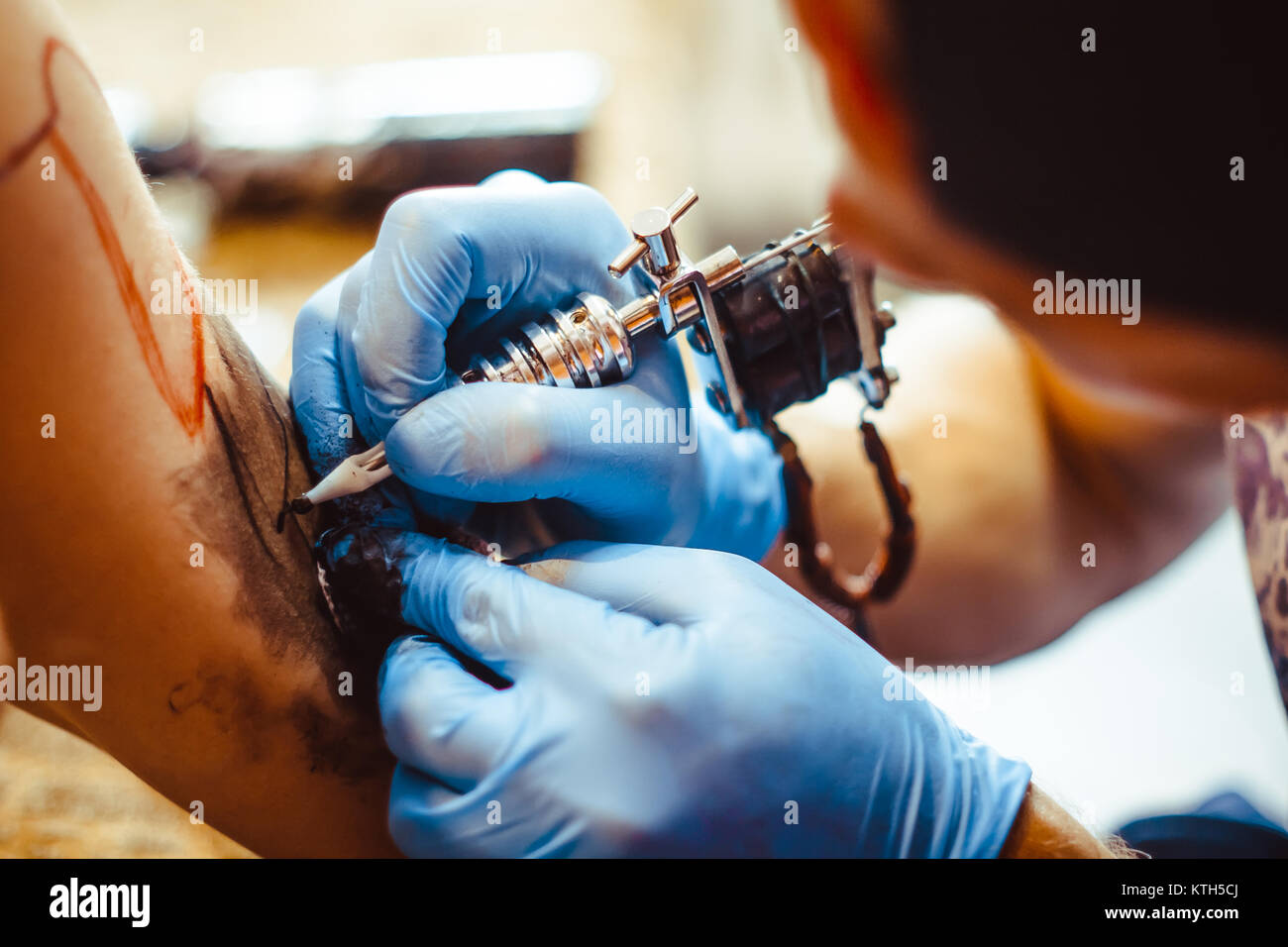 The tattoo artist makes a tattoo on the client's neck in the tattoo salon. The master does a tattoo in the studio. - Stock Image