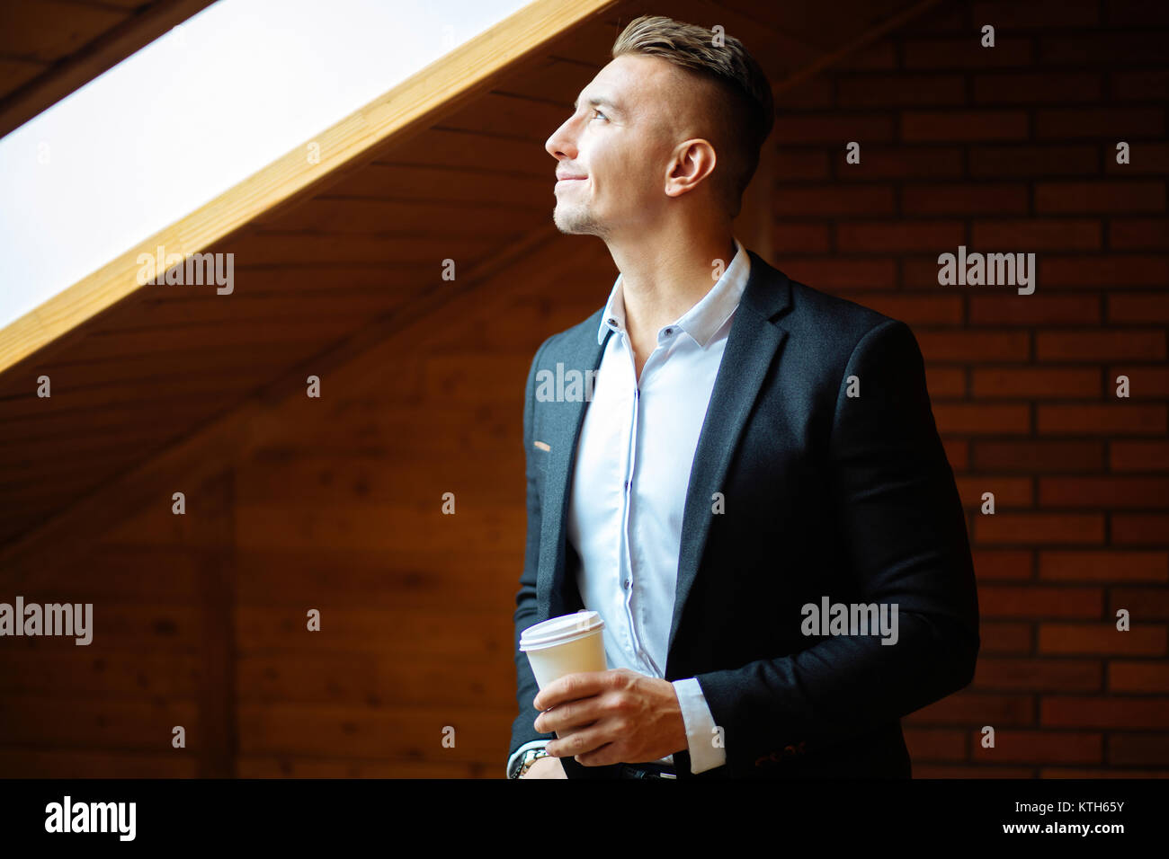 handsome businessman drinking coffee in home and looking away - Stock Image