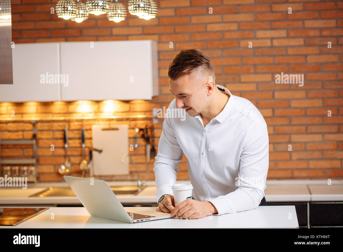 man working at home on some project, sitting at white table looking at laptop - Stock Image
