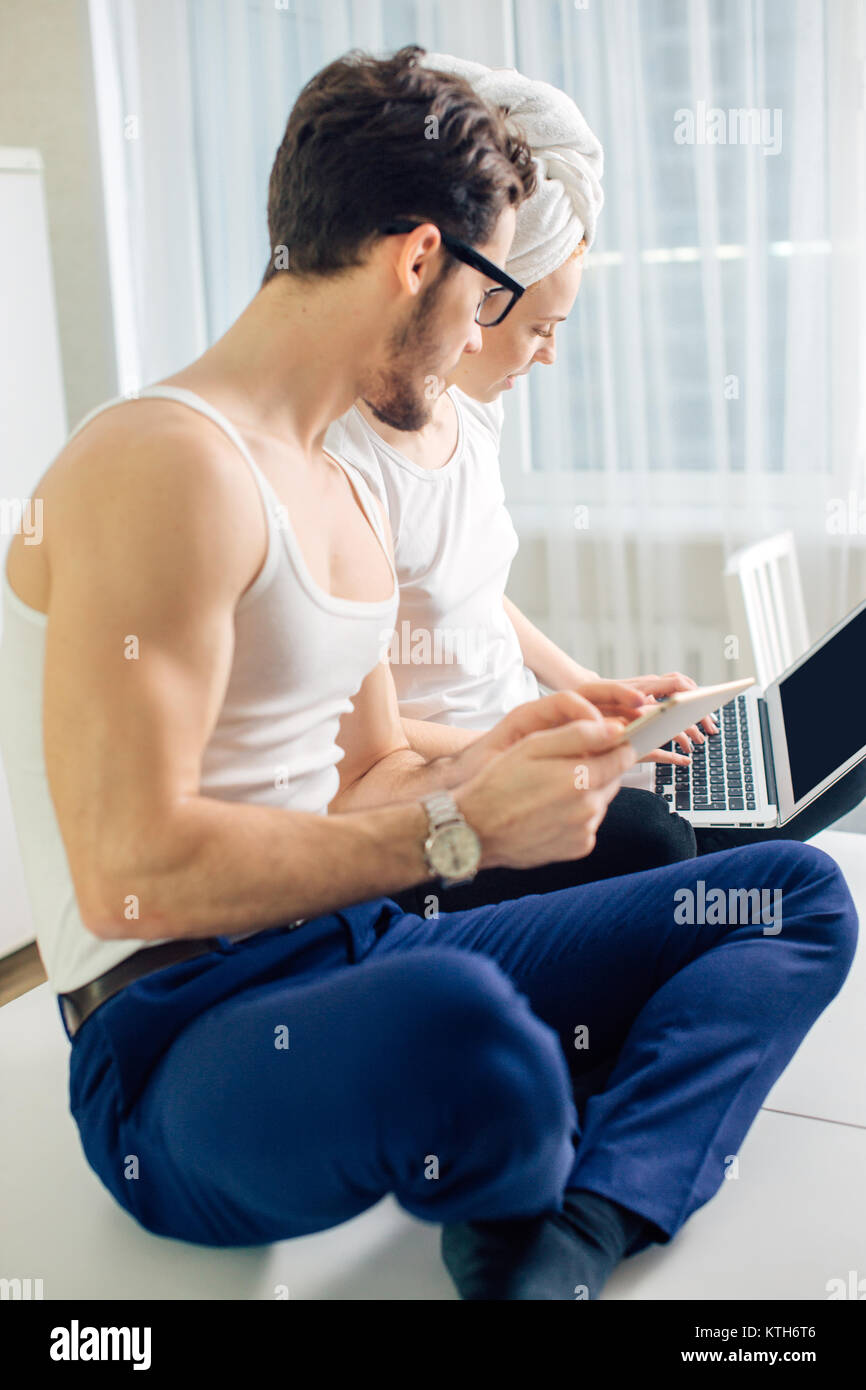 man holding tablet spying his girlfriend's laptop while she is typing message - Stock Image