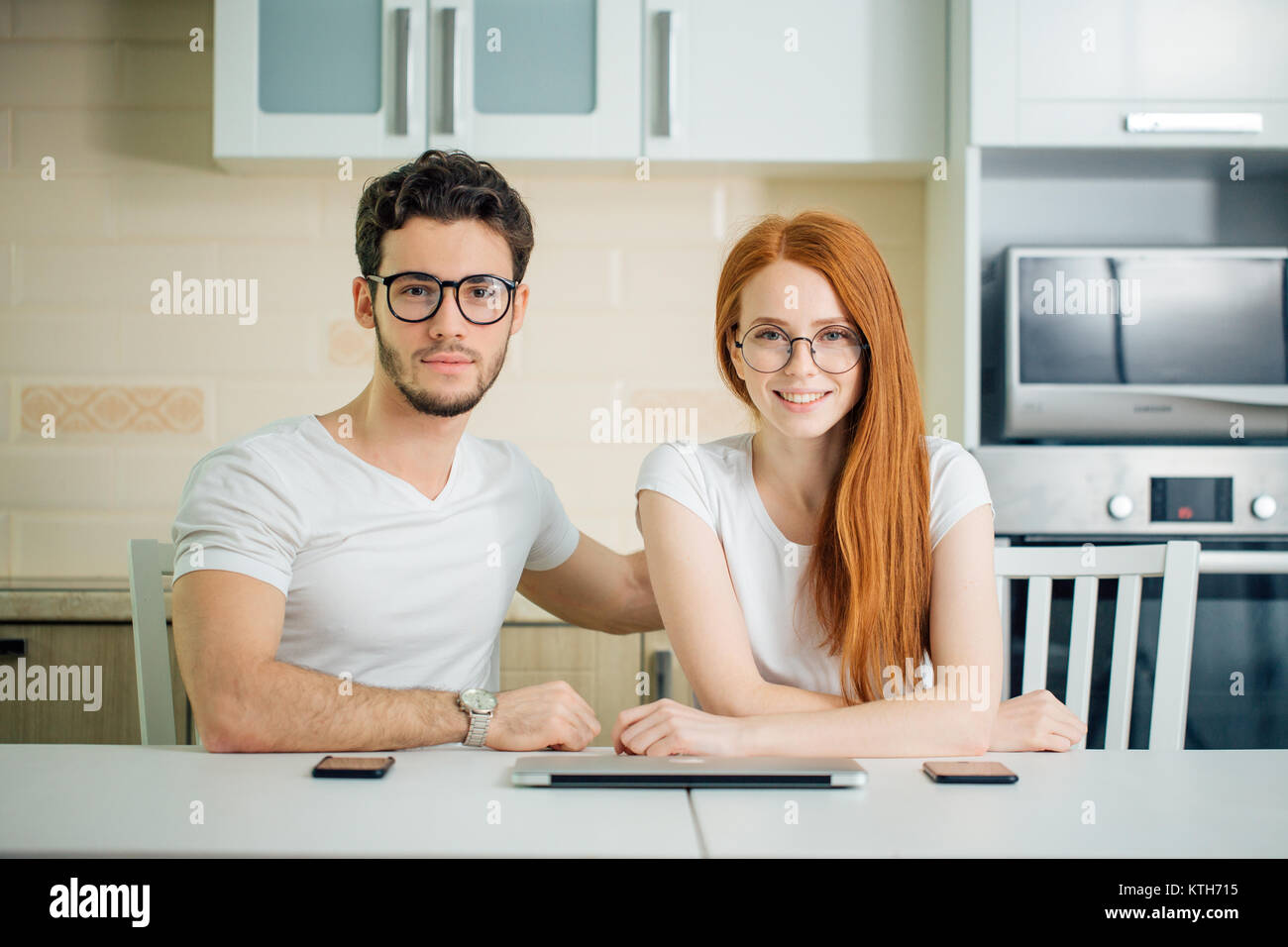 happy couple prepare to use laptop in kitchen at home - Stock Image