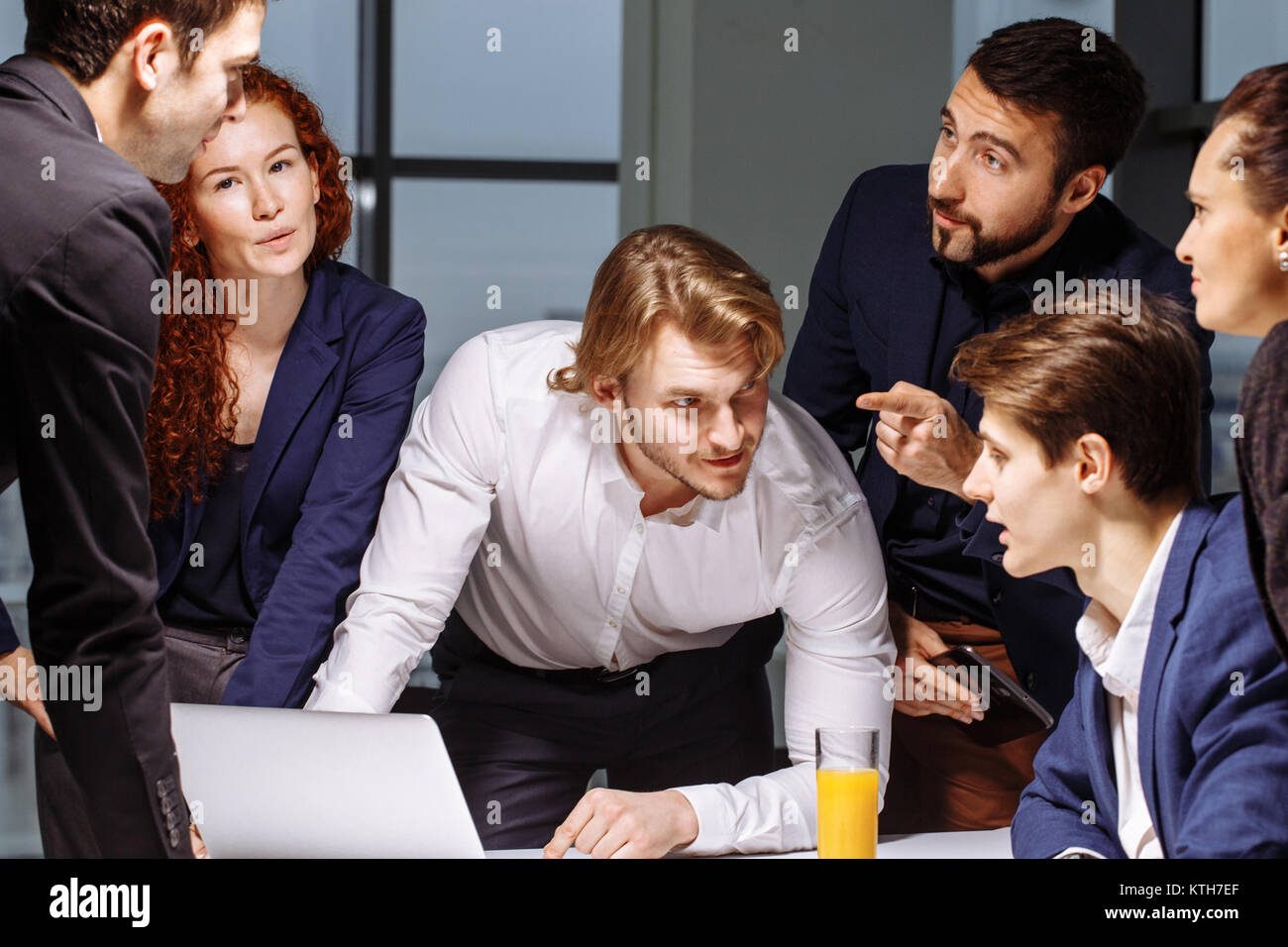 Smiling Female And Handsome Male Co-Workers Sitting At Table, Looking At Laptop - Stock Image
