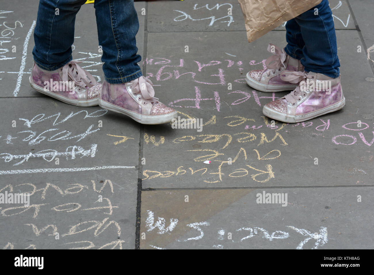 """""""Refugees are welcome here"""" and """"Help refugee children"""" messages are written on the pavement by children protesting - Stock Image"""