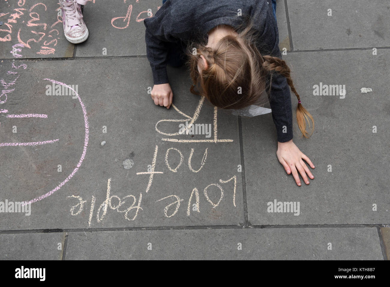 A child protester is writing anti-Trump and anti-racism message reading 'Love people not Trump' on the pavement - Stock Image