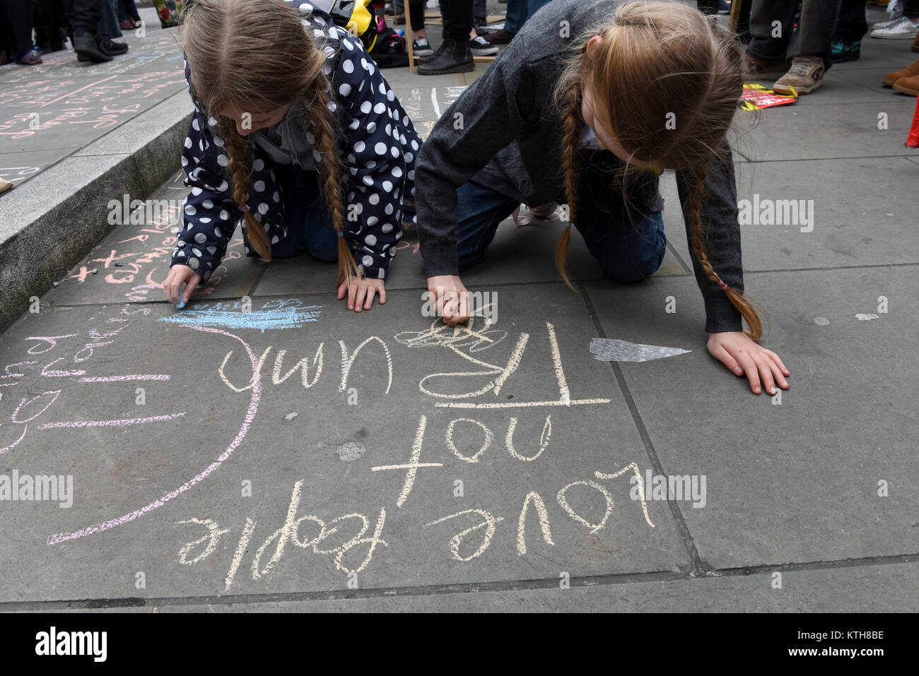 Little girls, sisters Honey and Bluebelle, are writing anti-Trump and anti-racism messages on the pavement during - Stock Image