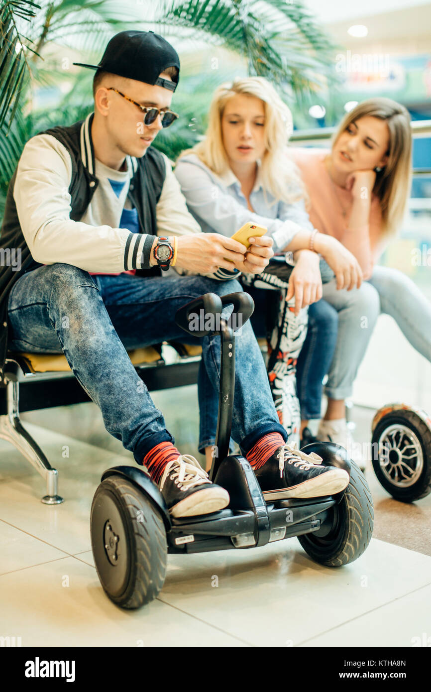 Group Of People On Electric Scooter Hoverboard Sitting At Bench And Stock Photo Alamy