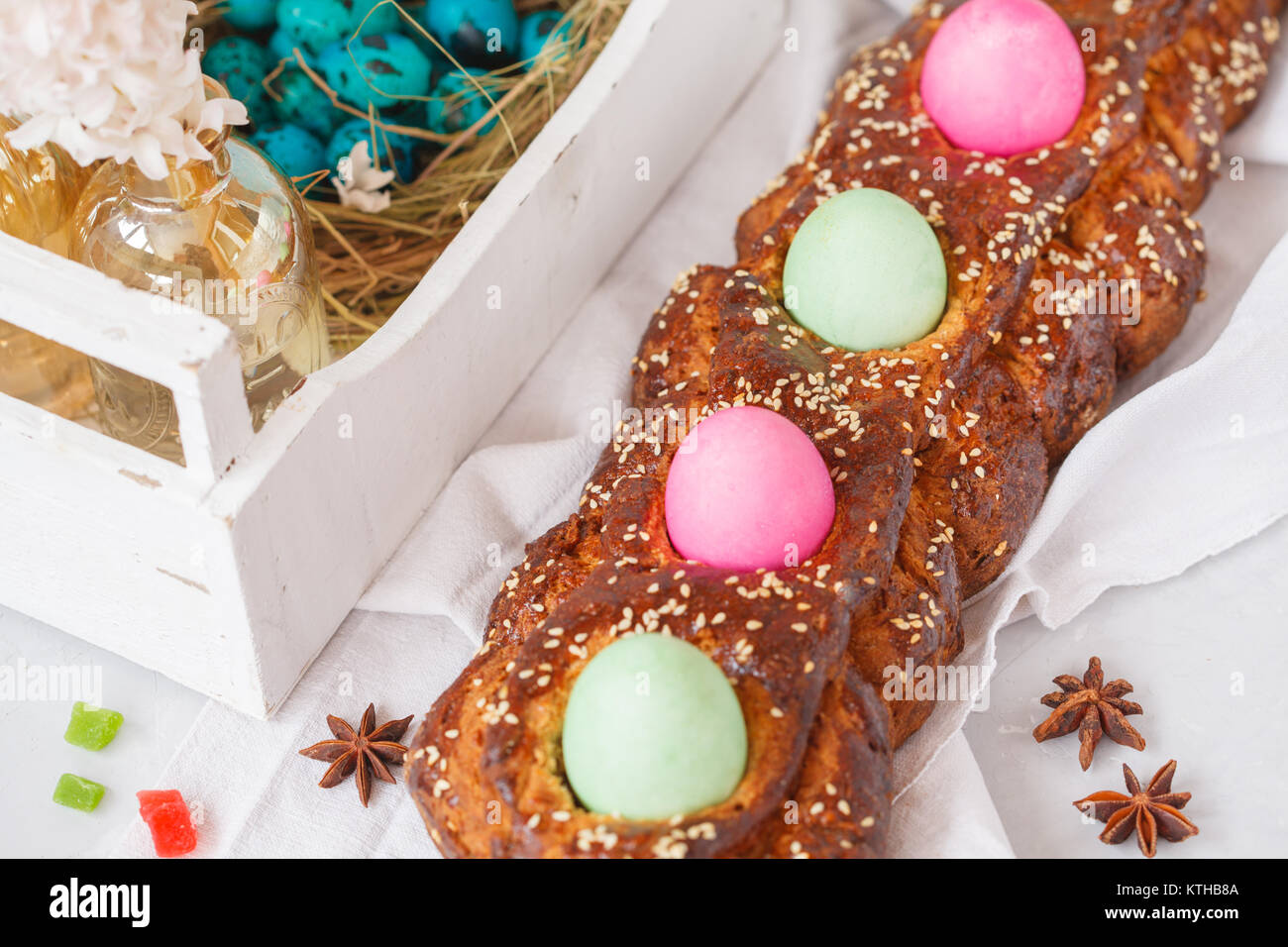 Traditional Greek Easter bread - tsoureki in Easter decorations with painted eggs and flowers. Easter Festival concept. - Stock Image