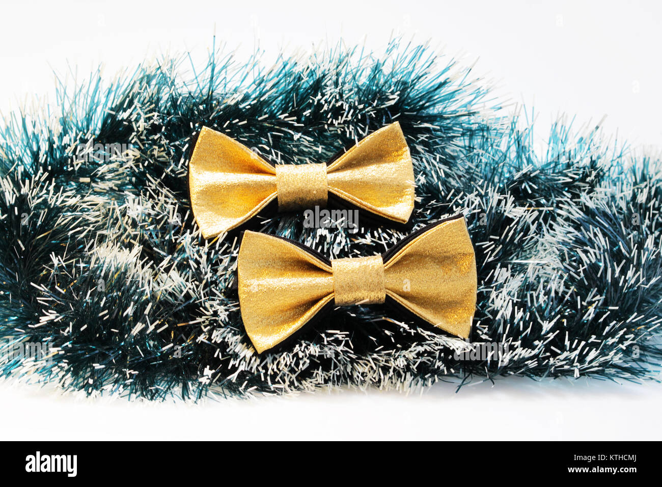 two festive gold butterfly bow tie against a background of green Christmas tree tinsel - Stock Image