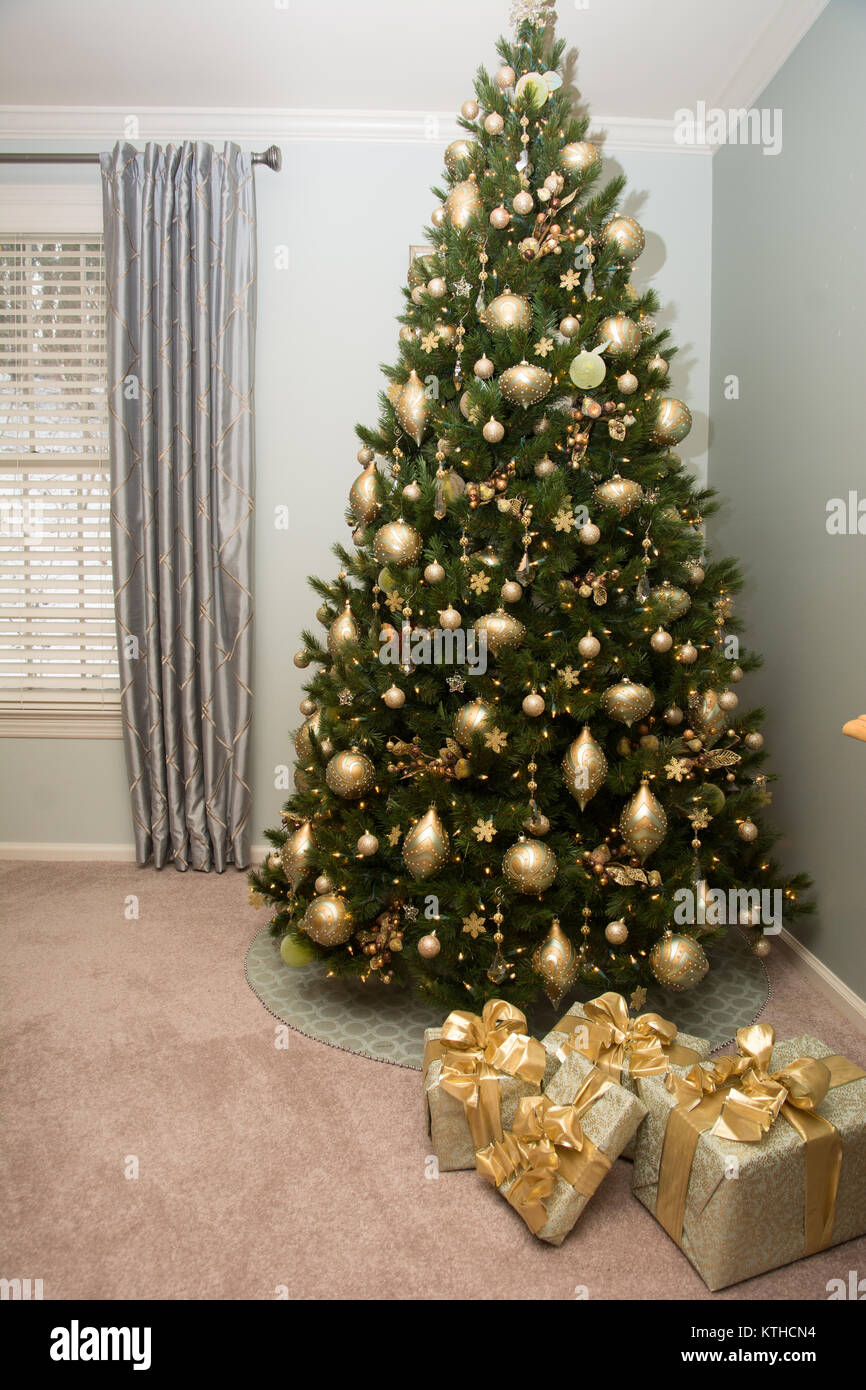 A beautifully decorated Christmas tree with gift package near it - Stock Image