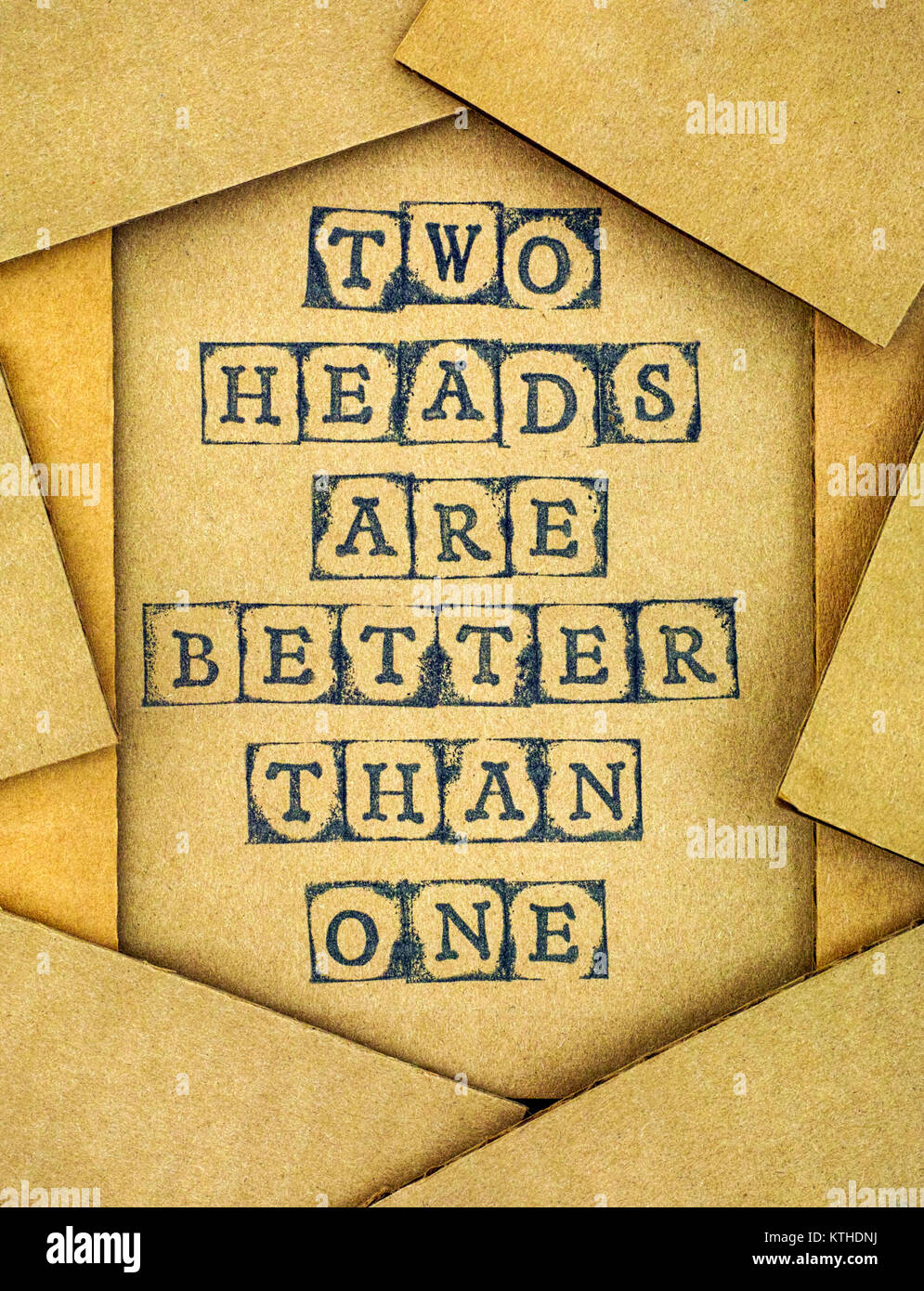 Phrase Two Heads Are Better Than One make by black alphabet stamps on cardboard with some piece of cardboard. - Stock Image