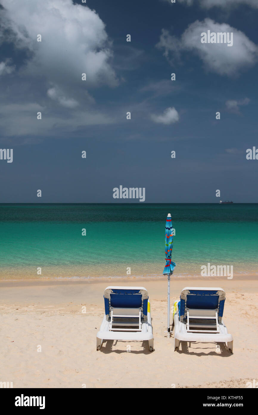 Beach chaise lounges and sea. St. George's, Grenada - Stock Image