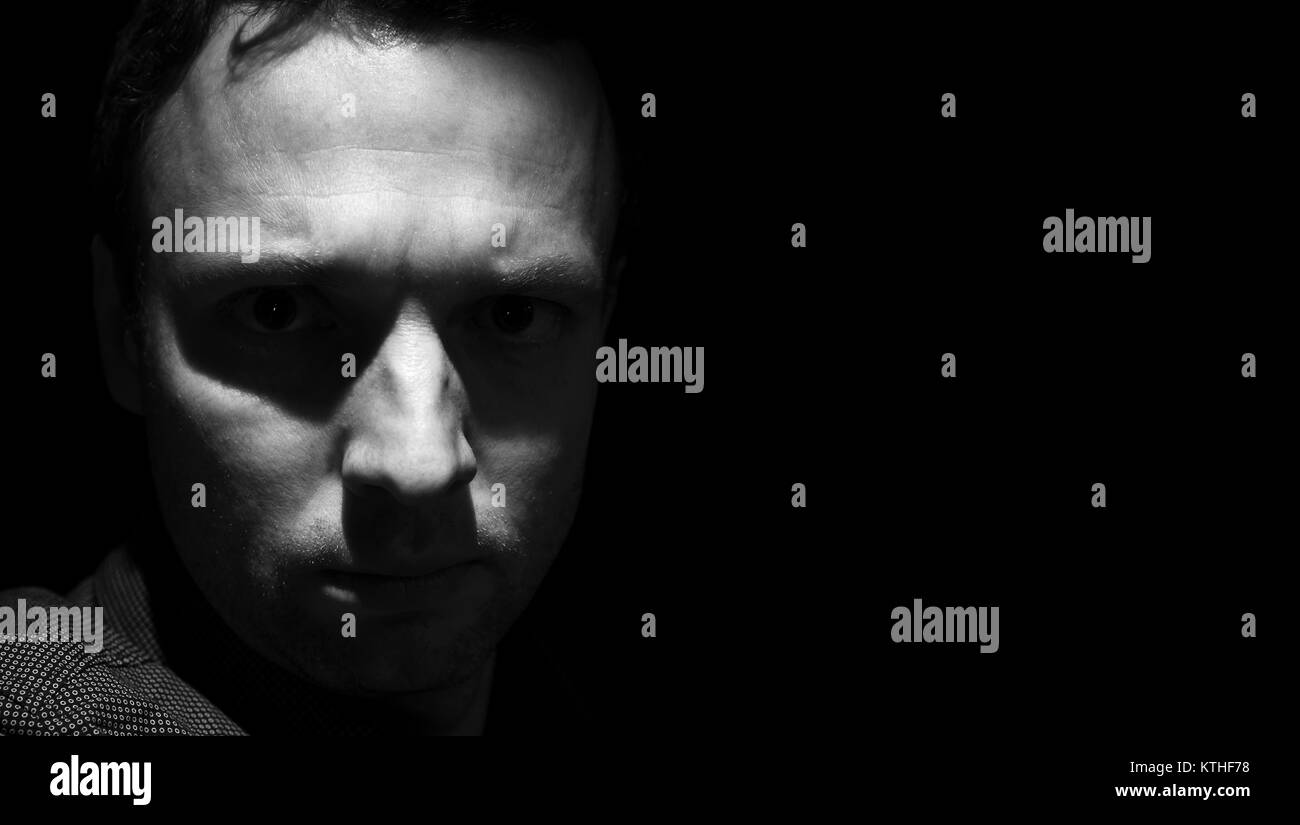 Closeup studio portrait of young adult man over black background low key black and white photo