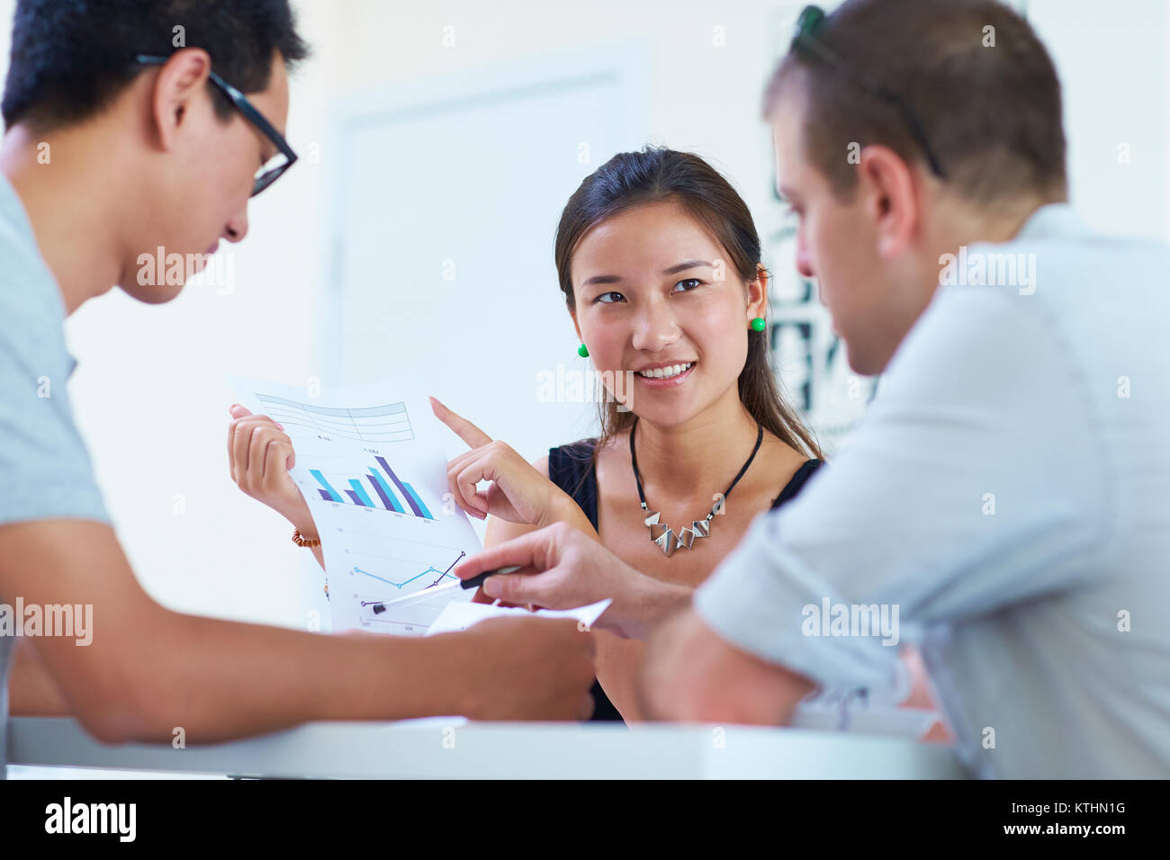 two asian business people having meeting with one white businessman