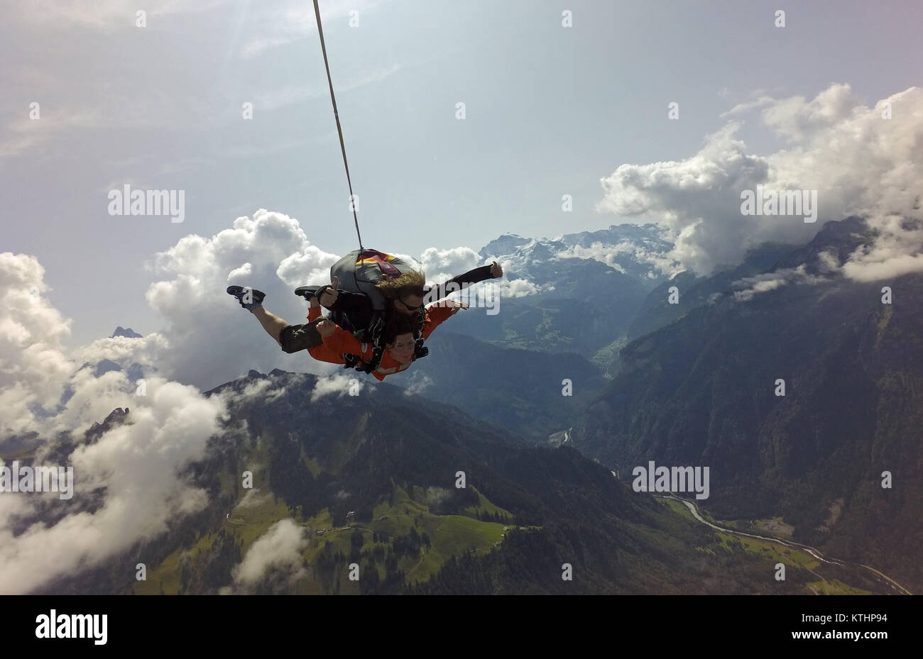 This tandem skydiving team is enjoying the scenic flight over a beautiful mountain and lake area. Check out the - Stock Image