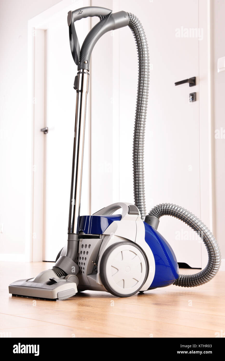 Canister vacuum cleaner for home use on the floor panels in the apartment. - Stock Image