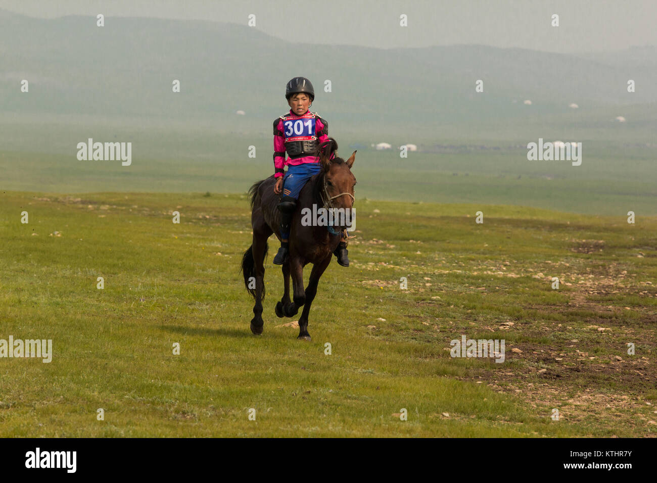 Boys of age 6 - 12 are used as riders during Naadam horse race. They and the horses are specialy trained and both - Stock Image