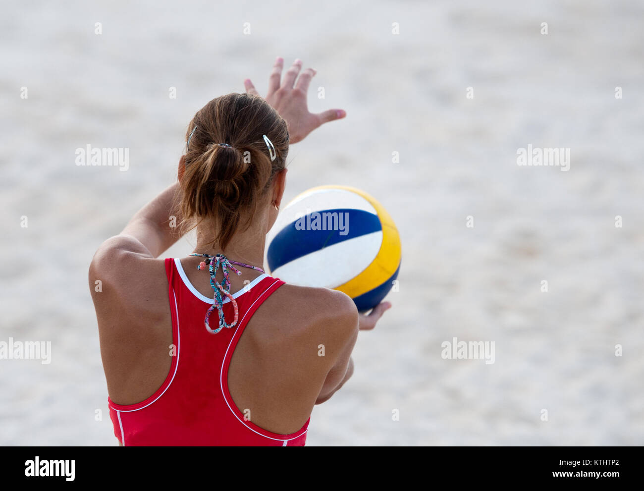 Young unrecognizable female athlete ready to serve on a beach volley game. - Stock Image
