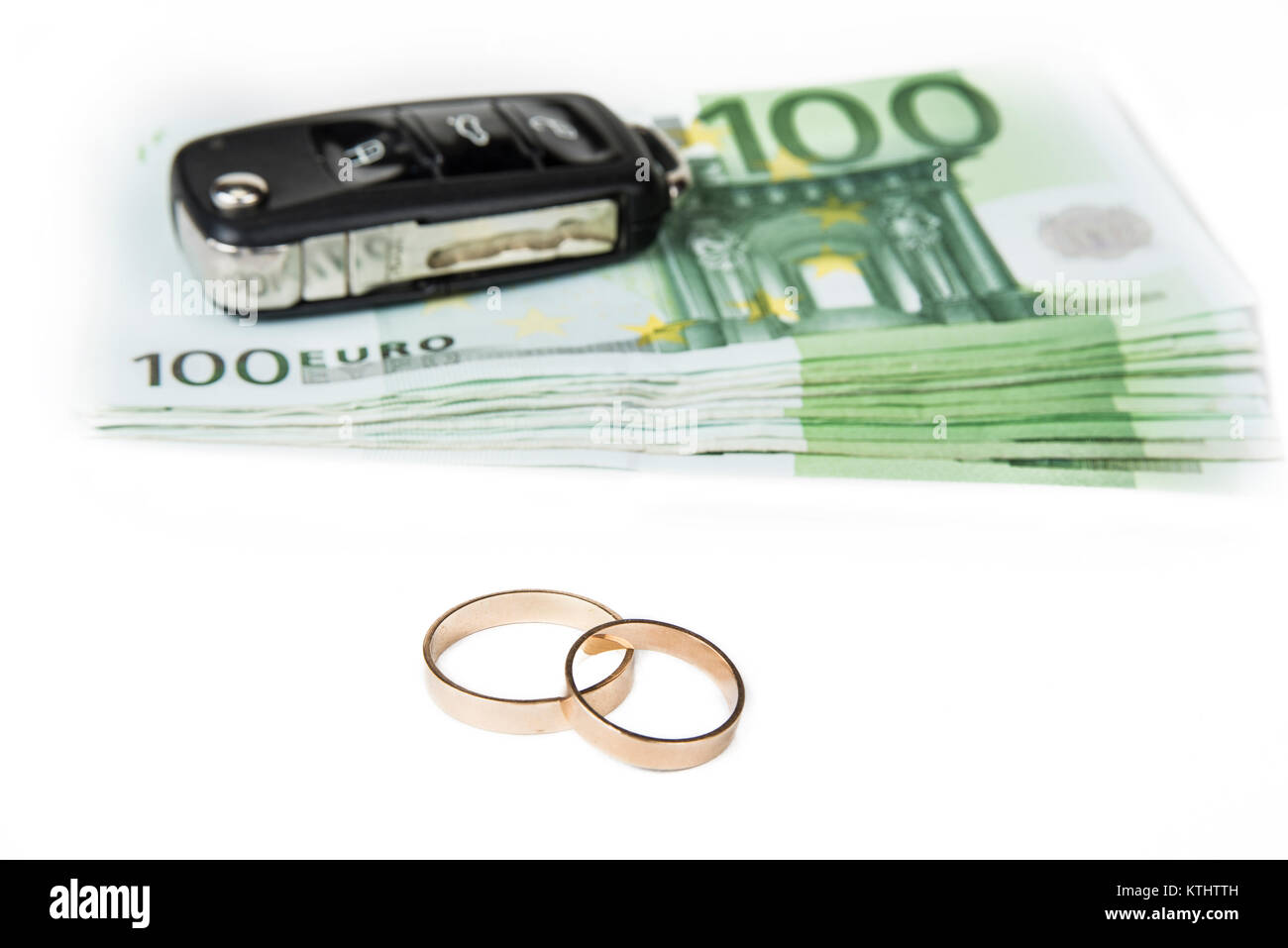 Gold digger concept. Money, car and wedding rings. - Stock Image