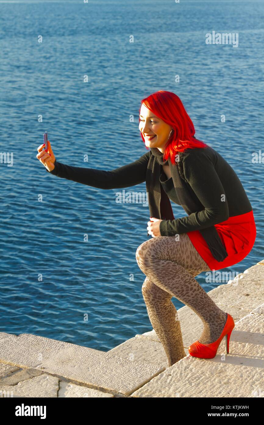 Feminine takes selfie photo with smarphone camera smiling smile happy happiness enthusiastic positive feeling model-released release alpfabet Stock Photo