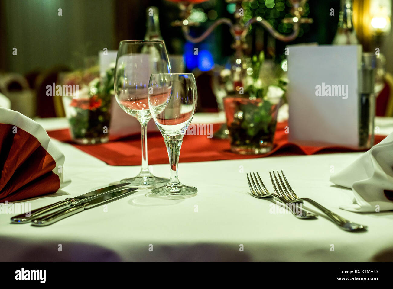 Banquet with red table setting Red tablecloth, white dishes, silver cutlery and glasses plus some decorations white - Stock Image