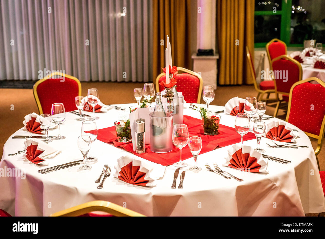 Banquet with red table setting Red tablecloth, white dishes, silver ...