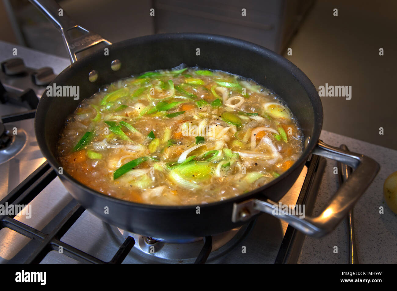 Vegetable soup simmering in pan on hob - Stock Image