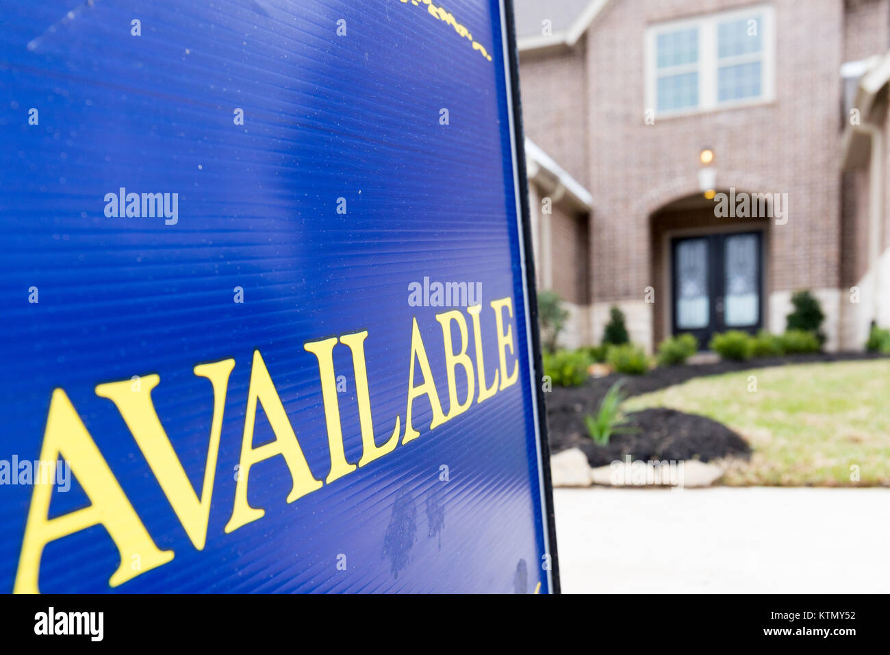 Available sign posted in front a new construction house - Stock Image