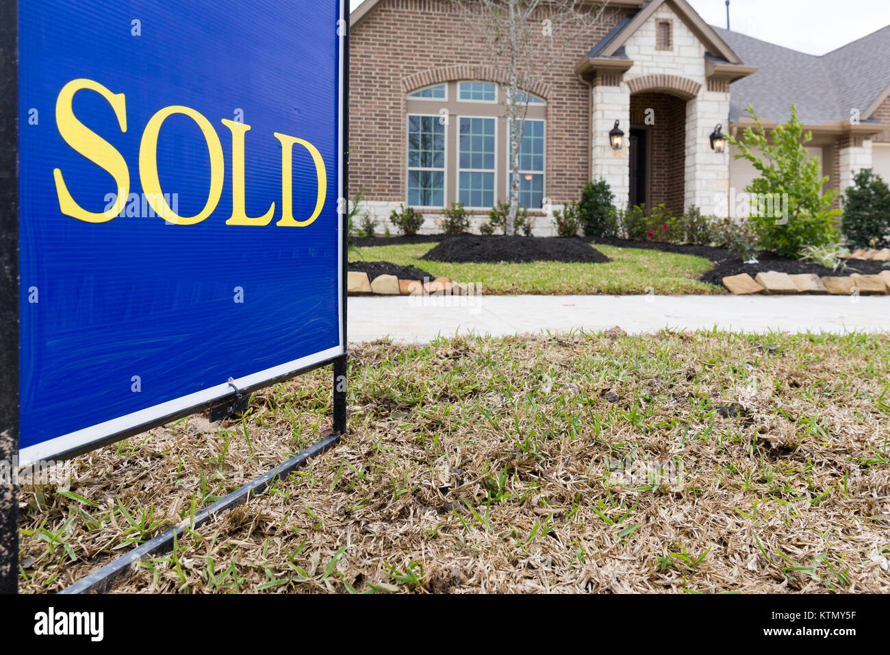 Sold sign posted in front a new construction house - Stock Image