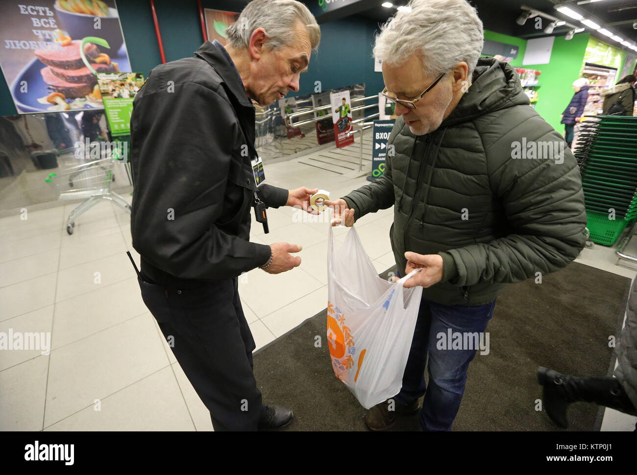 St Petersburg, Russia. 28th Dec, 2017. A security guard examines a customer's bag outside a Perekrestok supermarket. Stock Photo