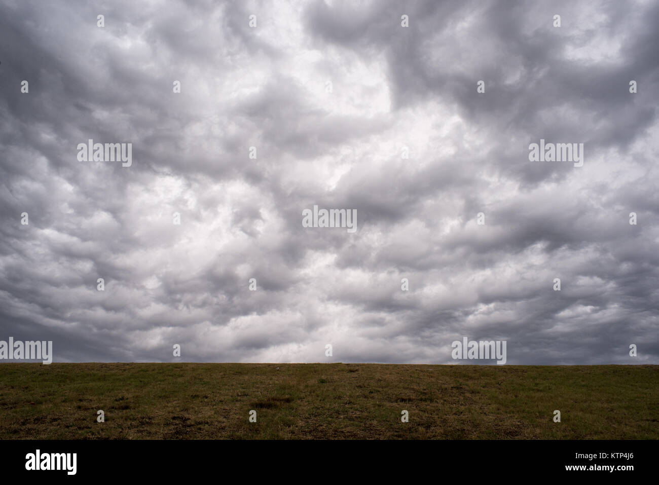 Outdoor view of a cloudy sky behind an embankment - Stock Image