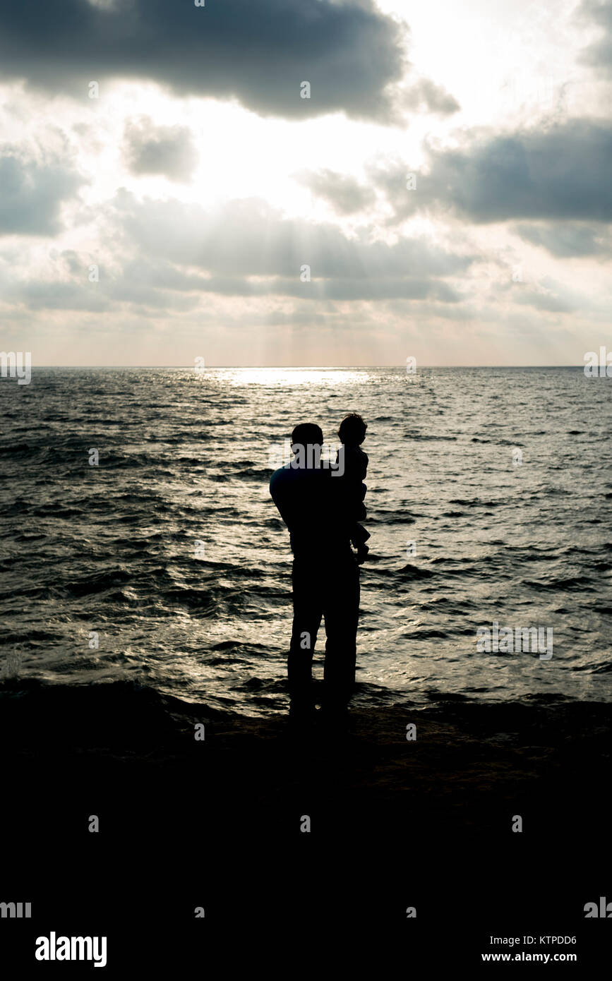 Tel Aviv, Israel. 2 July, 2015. A father and son look out over the Mediterranean sea at sunset.. Credit: Ian Jacobs/Alamy - Stock Image