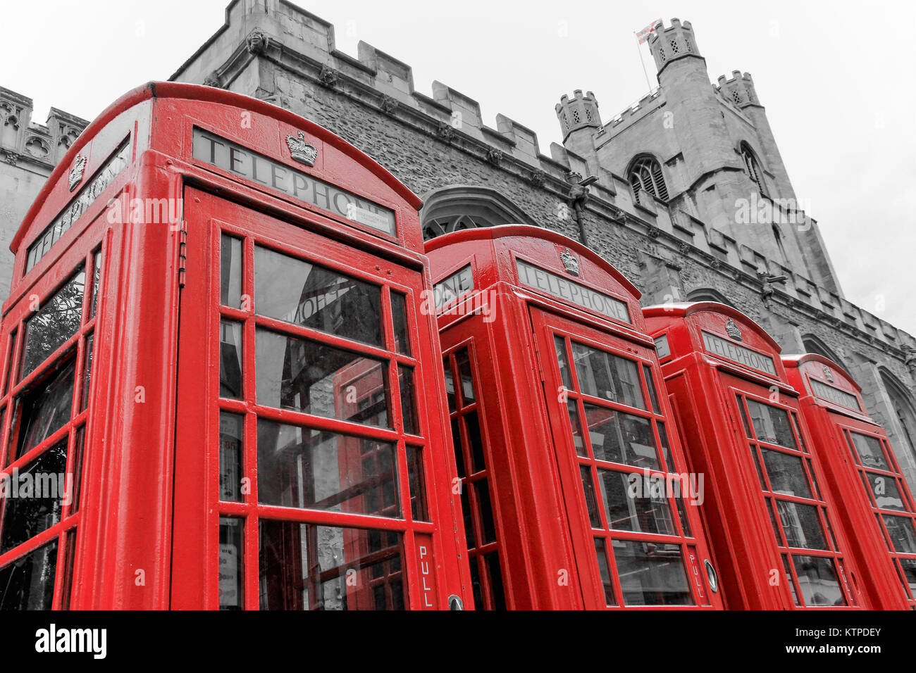Cambridge, England - 04 29 2017: A row of four classic K6 red phone boxes standing aside Great St. Mary's Church, - Stock Image
