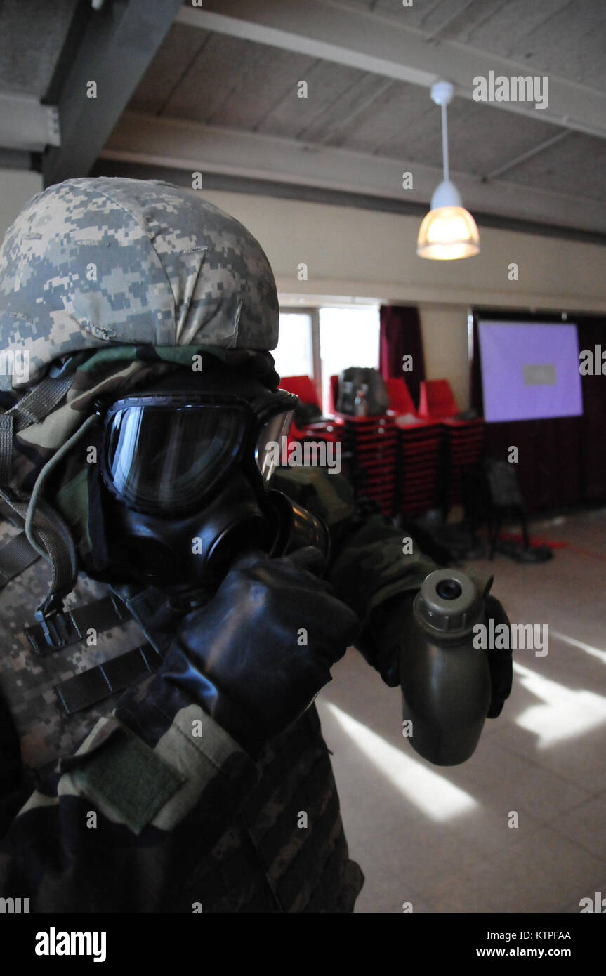 A female Soldier demonstrates how drink through her protective mask, while working through the Joint Service Lightweight - Stock Image