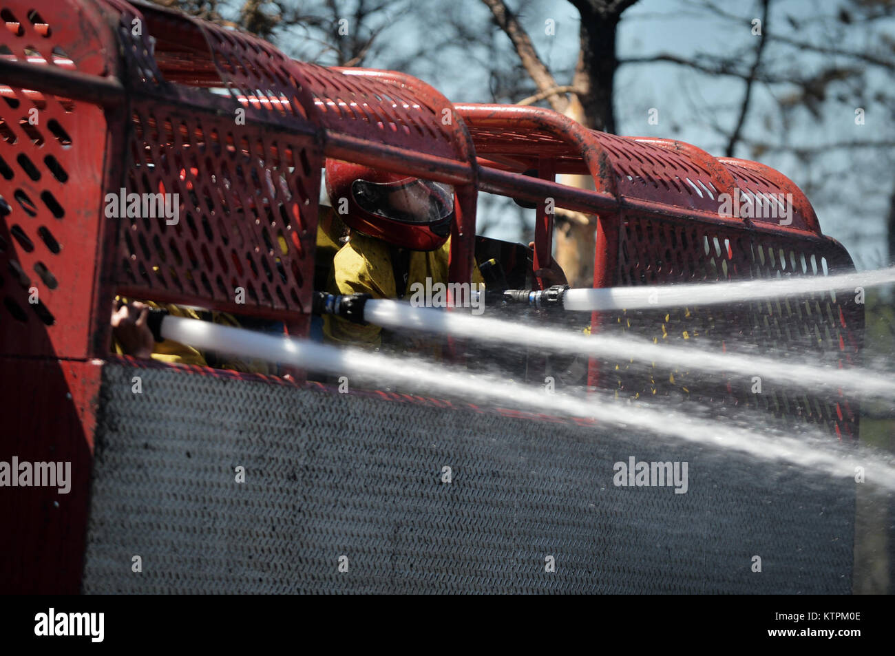 WESTHAMPTON BEACH, NY - Firefighters from the Riverhead Fire Department spray water on burning trees, grass and Stock Photo