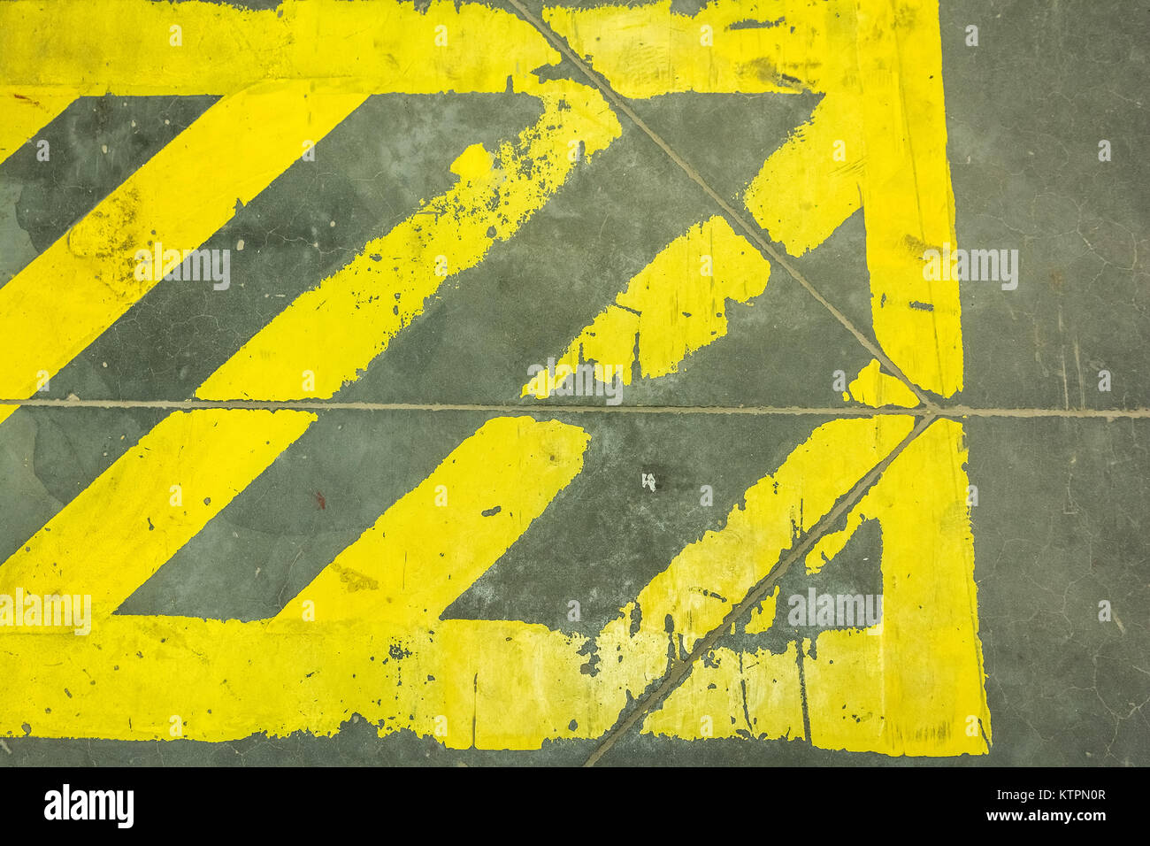 Close up yellow stripes prohibiting parking on grey surface - Stock Image