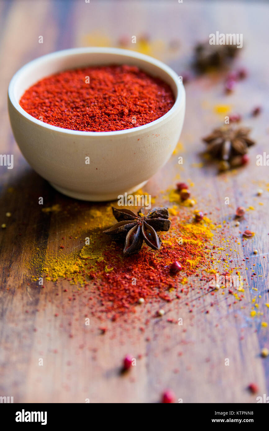 Close up white wooden bowl filled with paprika powder on dark wooden surface covered with anise and turmeric - Stock Image
